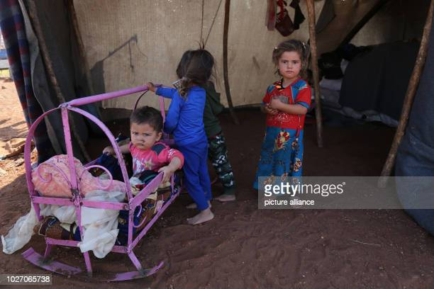 Children are seen inside their tent at a camp built by displaced people near a Turkish observation point after they were forced to leave the camps in...