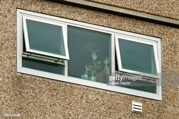 Children are seen looking out a window of the Flemington Towers Government Housing complex on July 06, 2020 in Melbourne, Australia. Nine public...