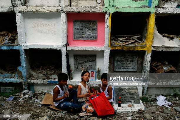 Children are seen near the graves of their relatives in a cemetery during the commemoration of All Saints' Day in Manila on November 1 2018 in Manila...