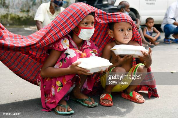 Children are seen on the road carrying free food packets during the new strict lockdown imposed to curb the spread of Covid-19 coronavirus in Dhaka....