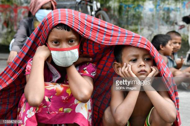 Children are seen on the road waiting for free food during the new strict lockdown imposed to curb the spread of Covid-19 coronavirus in Dhaka. This...