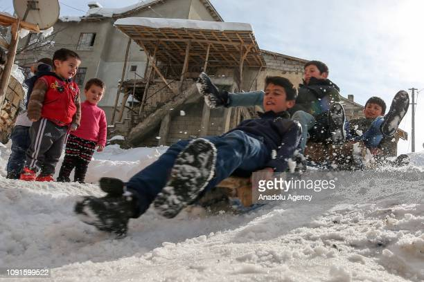 Children are seen on their sledges sledge in a sunny day after heavy snow as they slide down snow covered hill in Ikizler neighbourhood of Gevas...
