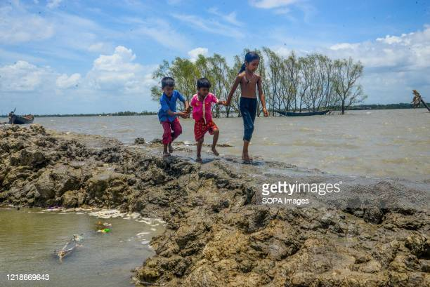 Children are seen walking through a muddy walk way at the coastal area after the landfall of cyclone Amphan. Thousands of shrimp enclosures have been...