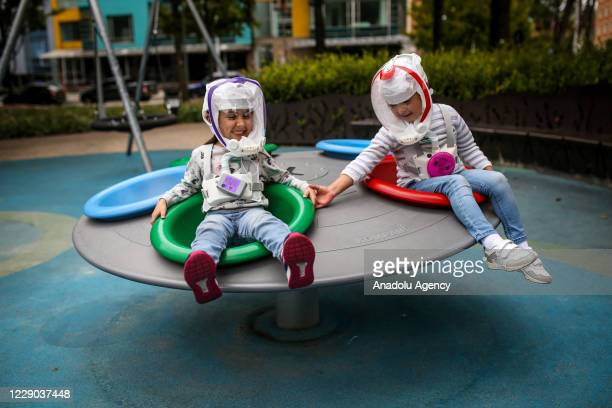 Children are seen with helmets similar to the ones used by astronauts which have designed by a group of Colombian engineers to be employed as a...