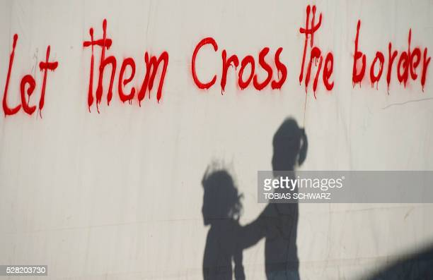 TOPSHOT Children are silhouetted next to a writing at a makeshift camp for migrants and refugees near the village of Idomeni not far from the...