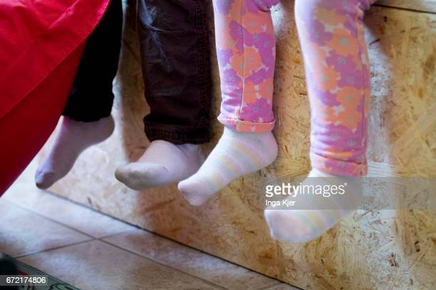 Children are sitting on a bench in a social PopupStore on April 20 2017 in Berlin Germany Founder of this project is the association 'Librileo...