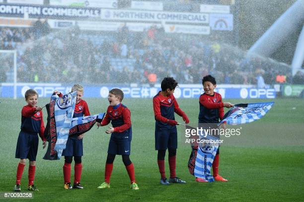 Children are sprayed by the sprinkler system before the English Premier League football match between Huddersfield Town and West Bromwich Albion at...