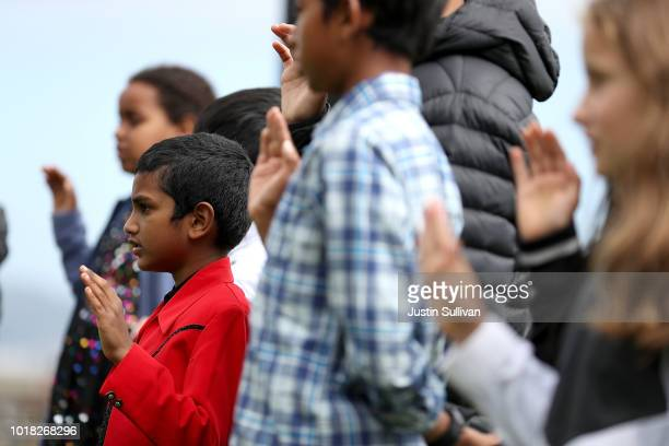 Attendees put pins on a map of the world during a naturalization ceremony for kids between the ages of 612 at Crissy Field near the Golden Gate...