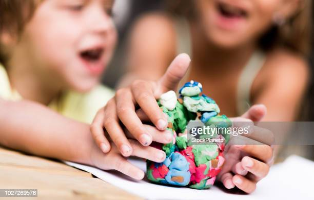children arguing about play dough - clay stock pictures, royalty-free photos & images