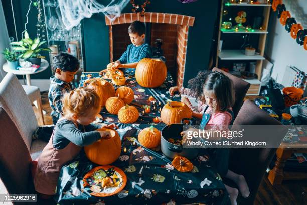 4 children around a table emptying the middle out of pumpkins. - halloween stock pictures, royalty-free photos & images