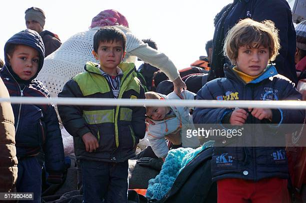 Children arrive along with other migrants and refugees aboard a Greek coast guard boat to the port of Mytilene on the Greek island of Lesbos on March...