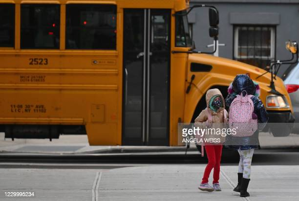Children arrive for class on the first day of school reopening on December 7, 2020 in the Brooklyn borough of New York City. - The novel coronavirus...