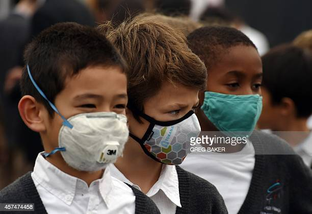 Children arrive wearing masks to protect them from pollution before performing at the groundbreaking ceremony for the new French International School...