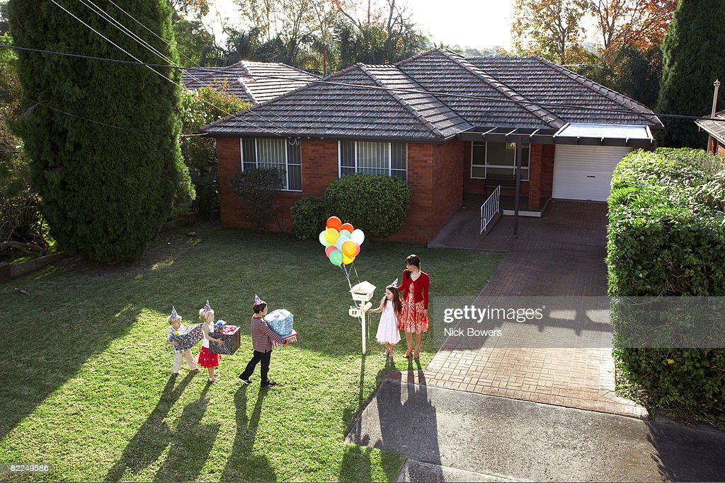 Children arriving at birthday party with gifts : Stock Photo