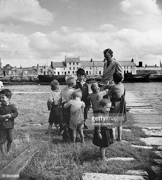 Children ask for pennies from a tourist on a quayside at Claddagh