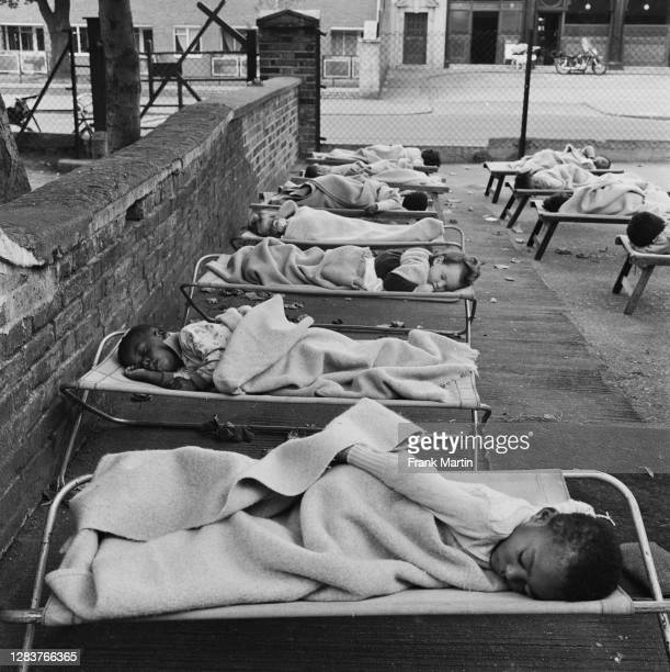 Children asleep in the playground of a day nursery in the Notting Hill area of west London, circa 1958.