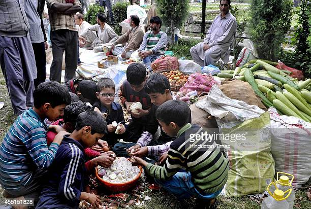 Children assist in chopping vegetables at a relief camp for flood affected people on September 9 2014 in Srinagar India More than 50000 people have...