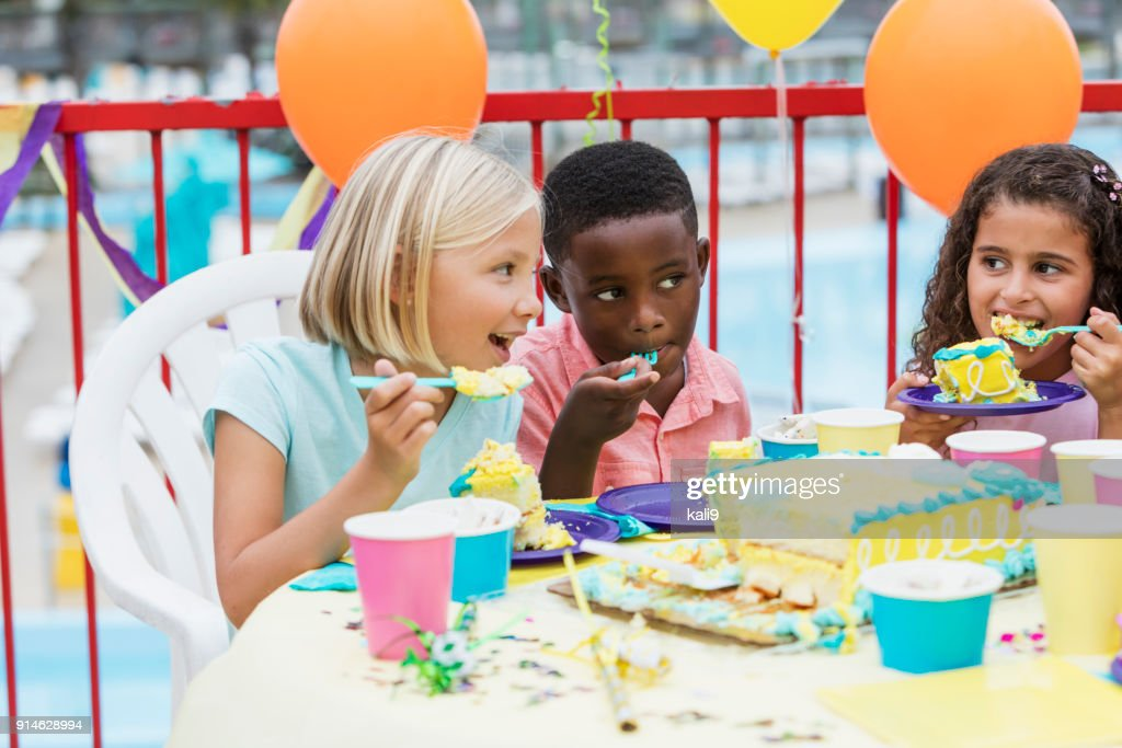 Children at a birthday party eating cake : Stock Photo