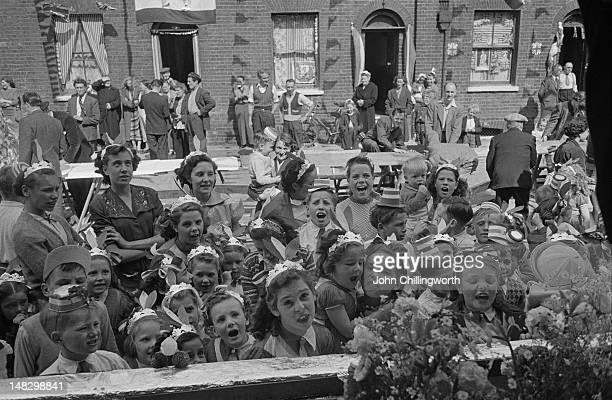 Children at a street party to celebrate the coronation of Queen Elizabeth II held in Morpeth Street in London's East End 2nd June 1953 Original...