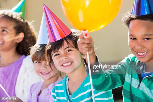 children at birthday party with hats and balloons - girl sitting on boys face stock photos and pictures