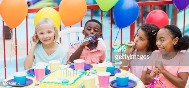 Children at birthday party with horns, laughing