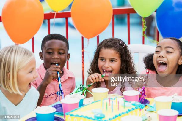 Children at birthday party with horns