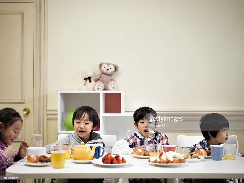 children at dining table, eating a breakfast. : ストックフォト