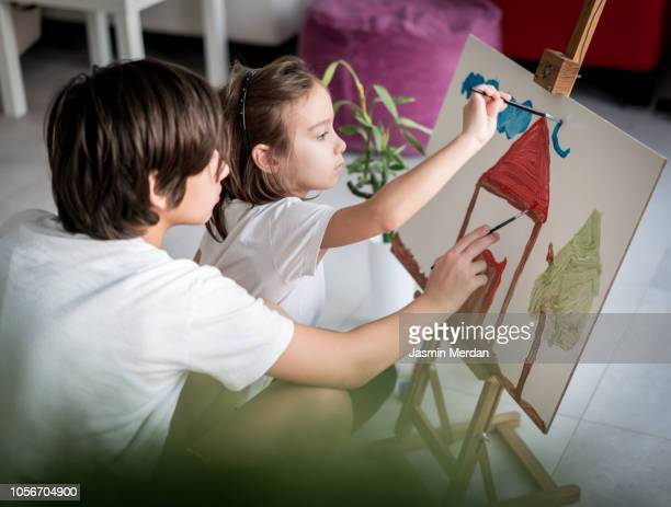 Children at home painting on canvas at home