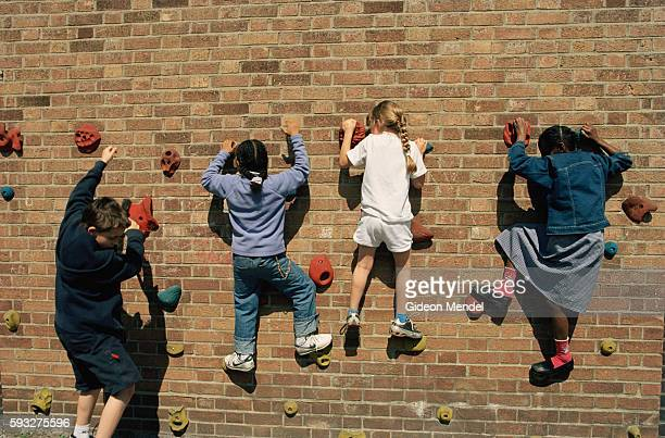 Children at Millfields Community School climb on a specially made climbing area of a wall in their playground during their breaktime The school is a...
