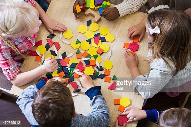 Children at preschool playing with colorful shapes