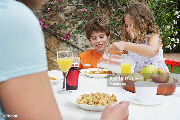 Children (5-6) at table girl pouring milk onto cereal