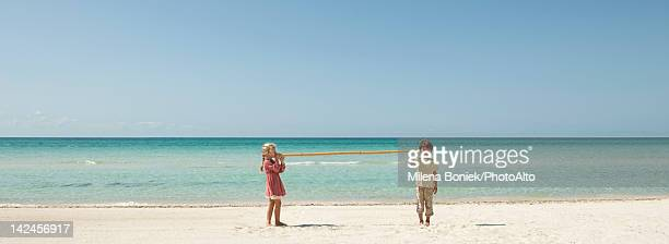 Children at the beach, talking to each other through long piece of bamboo