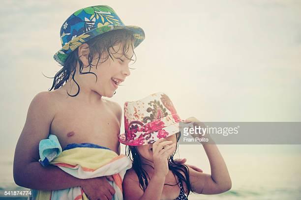 Children at the beach wearing fedoras.