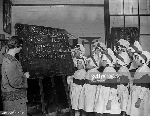 Children at the Bluecoat School at Colchester in Essex dressed in mob caps and pinafores watch their teacher write out a recipe for Christmas pudding