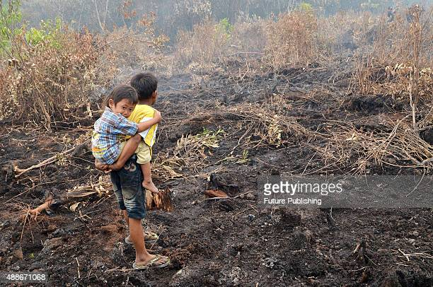 Children at the burnt site of the forest in Rimbo Panjang the Sumatran city of Pekanbaru on September 16 2015 in Riau Indonesia Indonesia on...