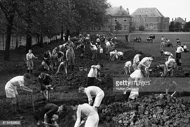 Children at the Harrow County School for Boys dig air raid trenches around the playing field