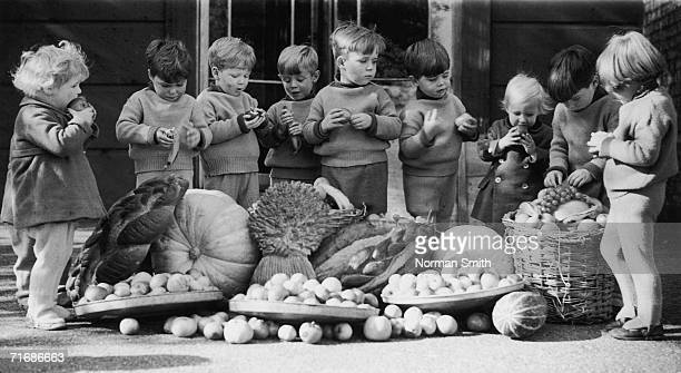 Children at the Leytonstone branch of the Homeless Children's Aid and Adoption Society tuck into a cornucopia of fruit sent by local churches from...