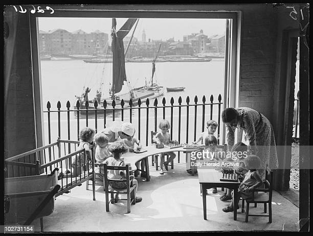 Children at the Port of London Day Nursery Wapping London 1933 Nursery children play games on a balcony overlooking the River Thames