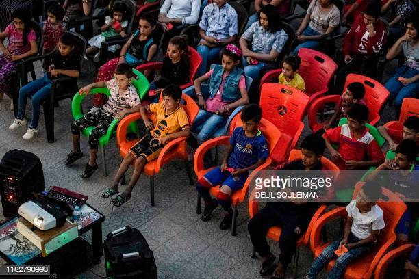 "Children attend a film screening as part of the mobile cinema ""Komina Film"" initiative organised by Syrian-Kurdish filmmaker Shero Hinde, at a school..."