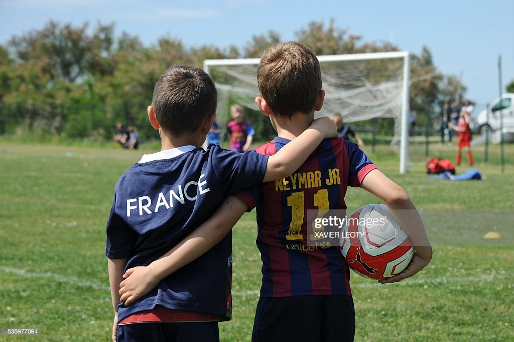 Children attend a football training on May 25, 2016 in Saint-Martin-de-Ré, on the Re Island, western France. The national football team of Spain will have its base camp on the island for the upcoming Euro 2016 European football championships. / AFP / XAVIER