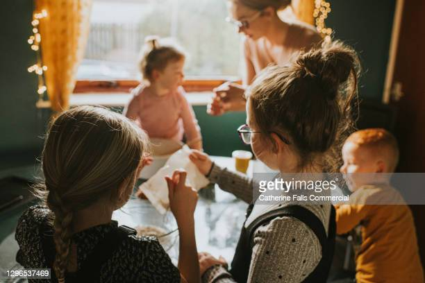 children baking at a table with mum supervising. daughters in foreground. - bad student stock pictures, royalty-free photos & images