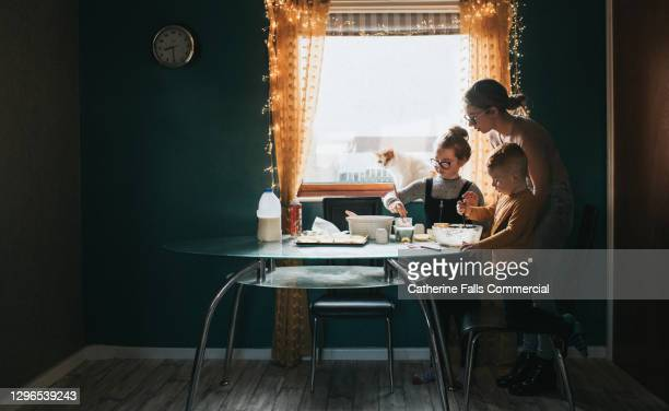 children baking at a table with mum supervising - table stock pictures, royalty-free photos & images