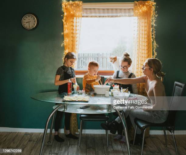 children baking at a table with mum supervising - mammal stock pictures, royalty-free photos & images