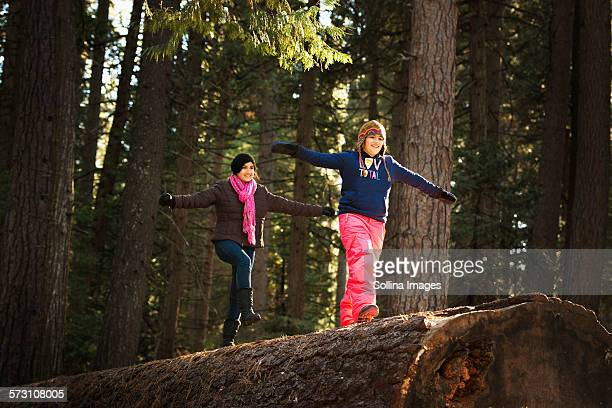 Children balancing on log in forest