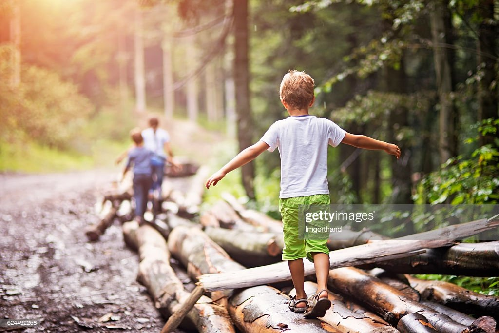 Children balancing on tree trunks : Foto de stock