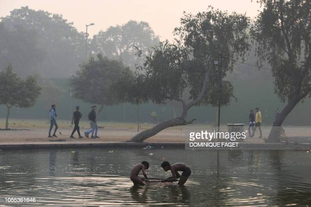 Children bathe in the water of a decorative shallow pool adorning the gardens surrounding the India Gate monument amid heavy smog conditions in New...