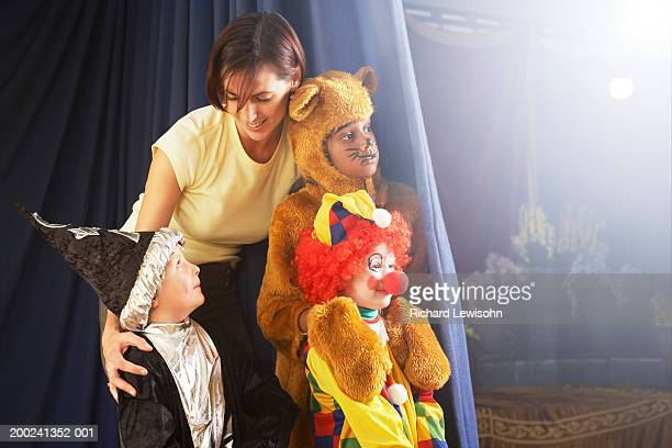 children (4-8) behind stage curtain, teacher talking to boy in wizard costume - school play stock photos and pictures