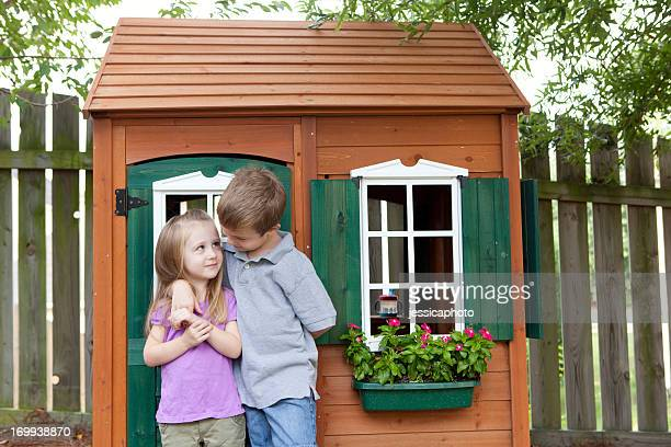 Children being friendly in front of wooden playhouse