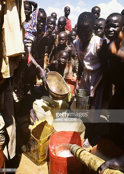 Children belonging to Mundari displaced ethnic group, wait for the water supply in September 1986 in a UNHCR refugee camp outside Juba, the capital...