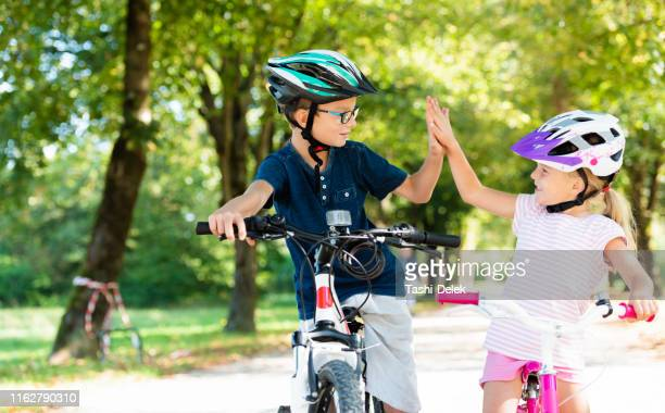 children bicycling high-five - cycling helmet stock pictures, royalty-free photos & images